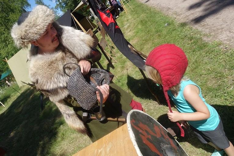 Barn i röd mössa ska få prova riddarhjälm av medeltidsklädd man.