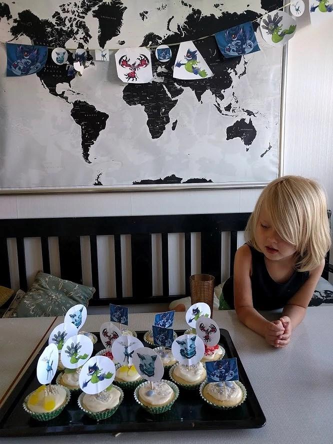 Barn tittar på plåt med cupcakes dekorerade med glasyr frosting, godis och strössel och Pokémonfigurer i papper.