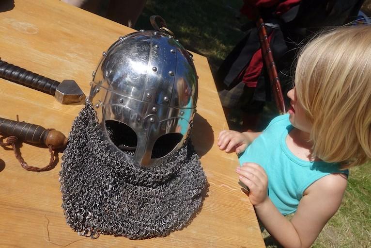 Barn tittar på en riddarhjälm av metall.