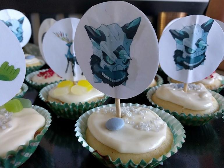 Plåt med cupcakes dekorerade med glasyr frosting, godis och strössel och Pokémonfigurer i papper.