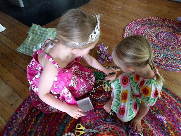 Flickor i blommiga klänningar tittar på halsband på färgglada mattor.