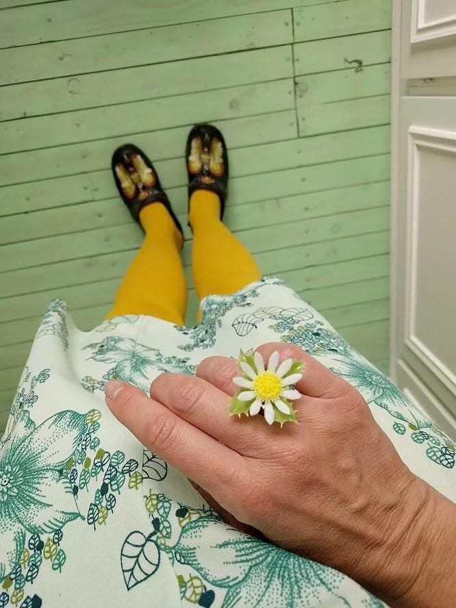 Skolavslutning i loppisfynd och träskor gula strumpbyxor handgjord ring i silver med plastblomma från retro ljusmanchett vintage klänning blommig mot mintgrönt retro golv.