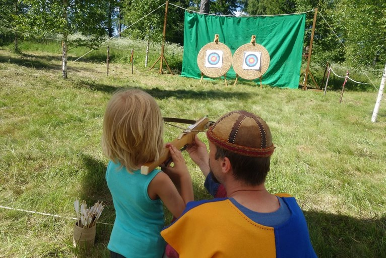 Barn provar att skjuta armborst med medeltidsklädd man.
