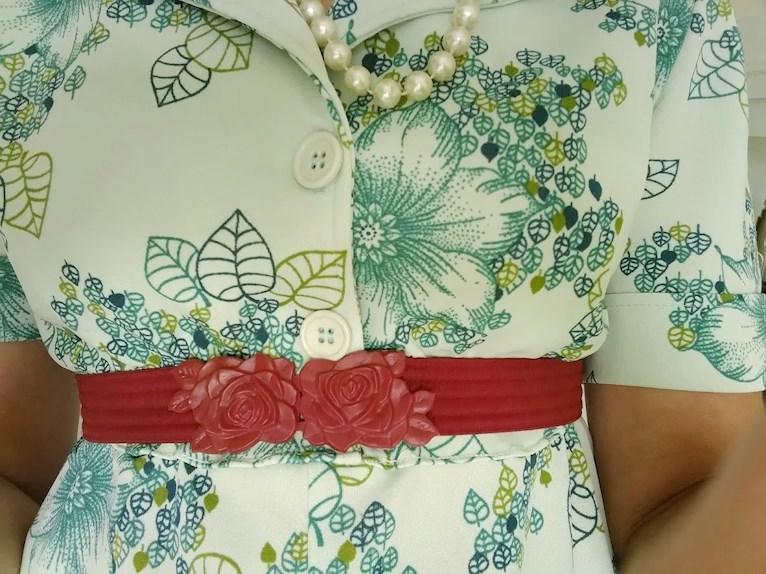 Skolavslutning i loppisfynd och träskor retro vintage klänning blommig i grönt och blått med rött vinrött bälte med rosor.
