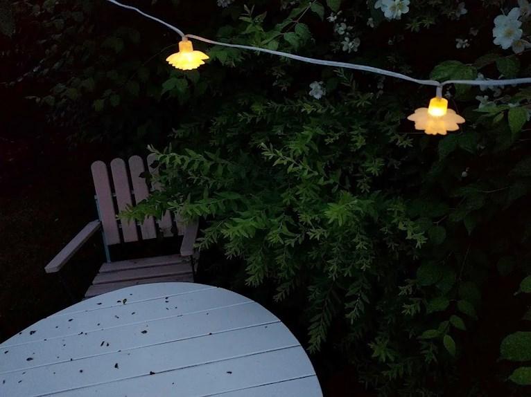 Renoverat grythyttan trädgårdsbord bord retro målat vitt fixat på plats i trädgården bland prästkragar och ännu ej tillfixade stolar på kvällen med lysande ljusslinga i form av blommor ovanför.