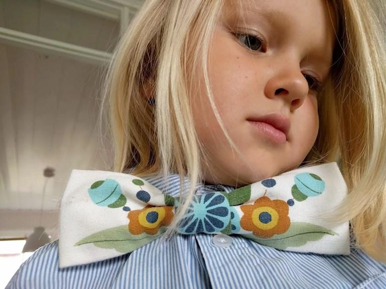 Skolavslutning i loppisfynd och träskor med kurbits hemsydd fluga av gardin mot randig blå skjorta på blont barn.