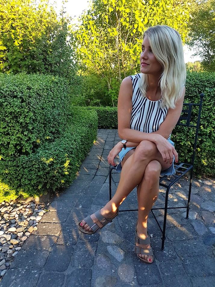 Sara Back i jeanskjol, randigt linne och birkenstock i en lummig trädgård sommaren 2018