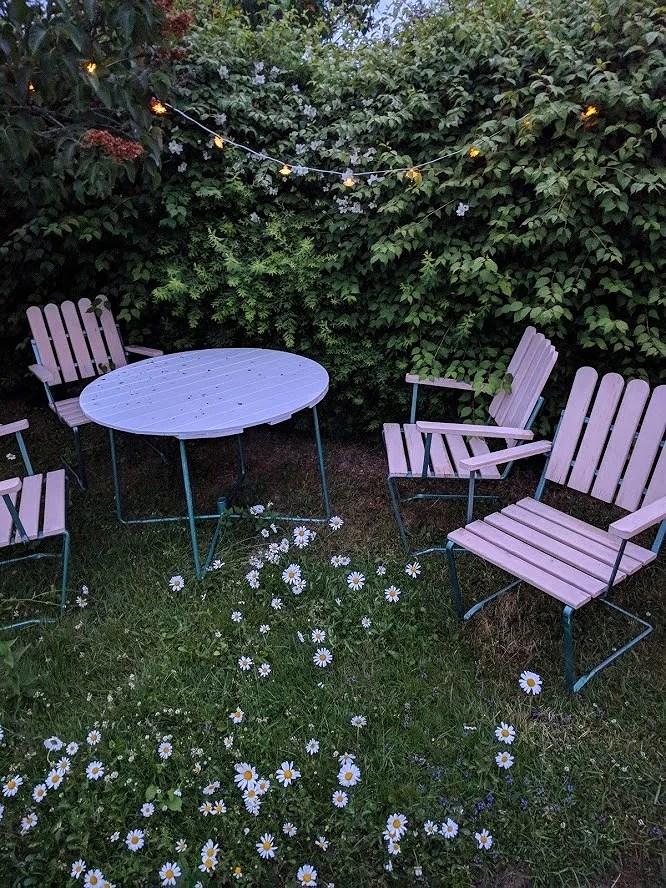 Renoverat grythyttan trädgårdsbord bord retro målat vitt fixat på plats i trädgården bland prästkragar och ännu ej tillfixade stolar på kvällen med lysande ljusslinga ovanför.