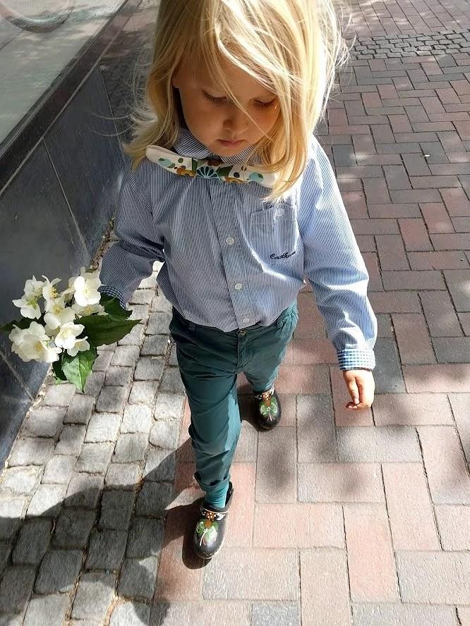 Skolavslutning i loppisfynd och träskor med kurbits fluga sydd av retro gardin mot blå skjorta på barn med blombukett i handen.