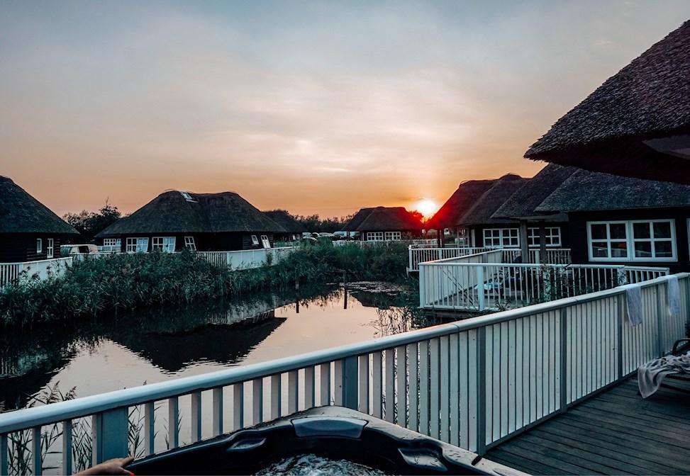 feriepark, hvidbjerg strand feriepark, jacuzzi, stråtag, solnedgang, feriehuse, hytter, stråtækte huse, sø