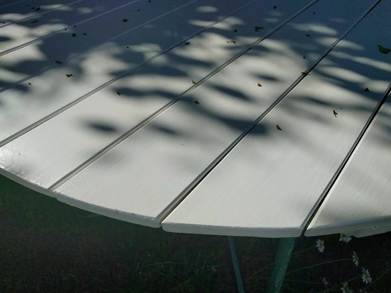 Renoverat grythyttan trädgårdsbord bord retro målat vitt fixat på plats i trädgården närbild med skuggspel..