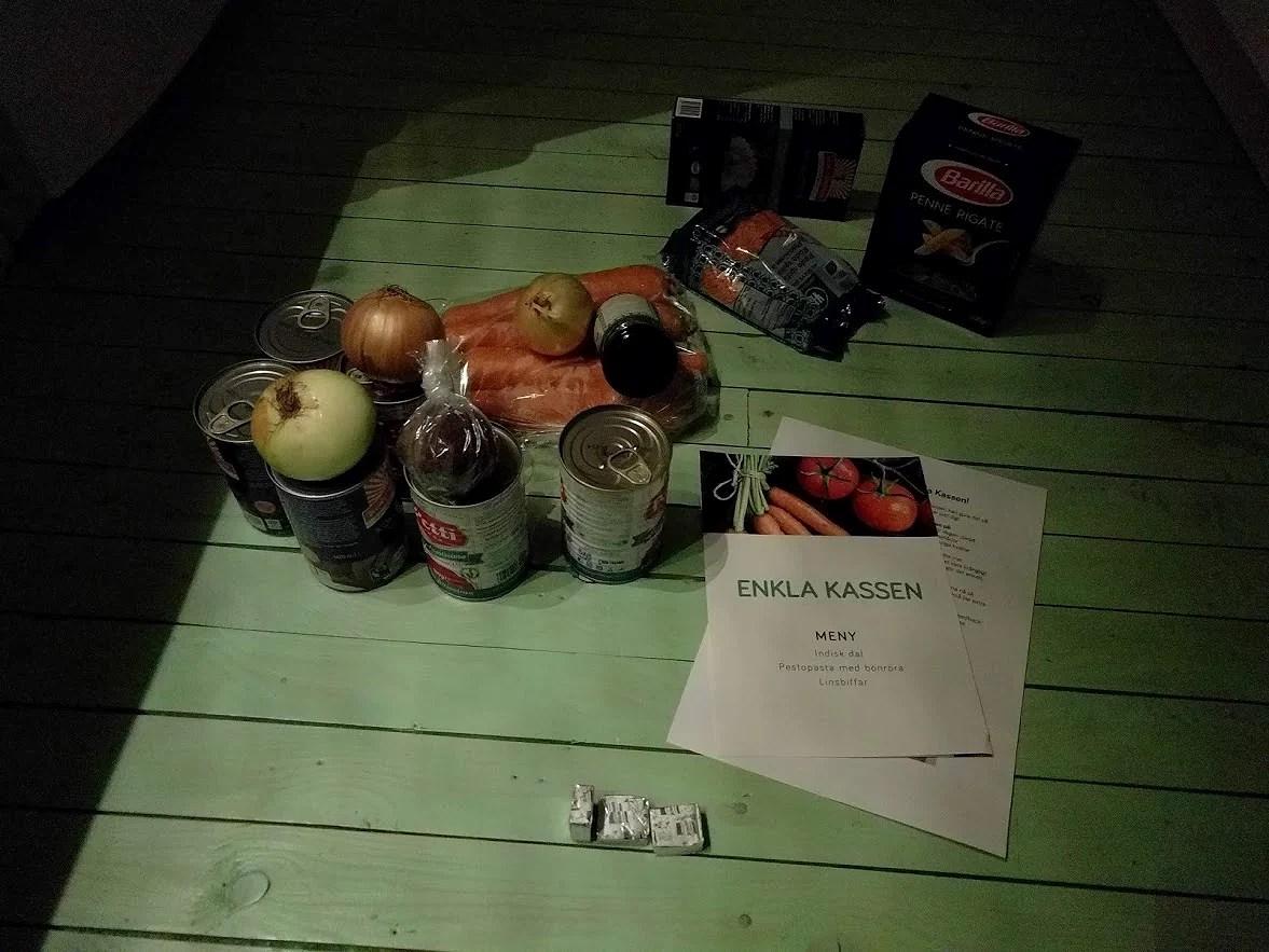 Enkla kassen vegansk matkasse i låda grönsaker, ris, pasta mycket ekologiskt urtekram och kung markatta på golvet i mörkret sent på kvällen.