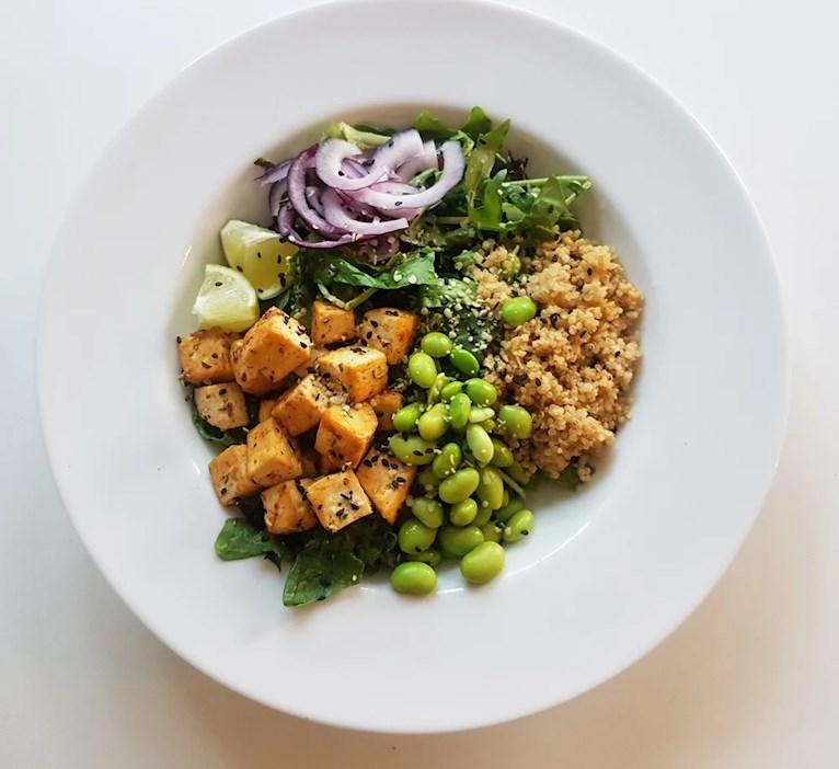 Vegansk tofubowl med qinoua, tofu, edamebönor, lime, avokado och sallad.