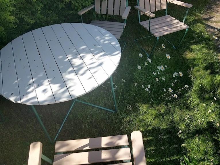 Renoverat grythyttan trädgårdsbord bord retro målat vitt fixat på plats i trädgården bland prästkragar och ännu ej tillfixade stolar sett ovanifrån.