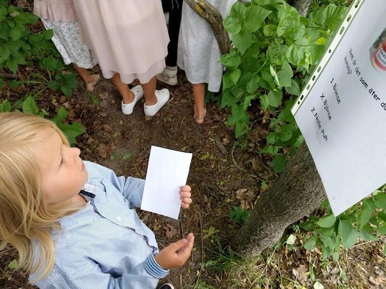 Skolavslutning i loppisfynd och träskor med kurbits barn svarar på frågor i tipspormenad.
