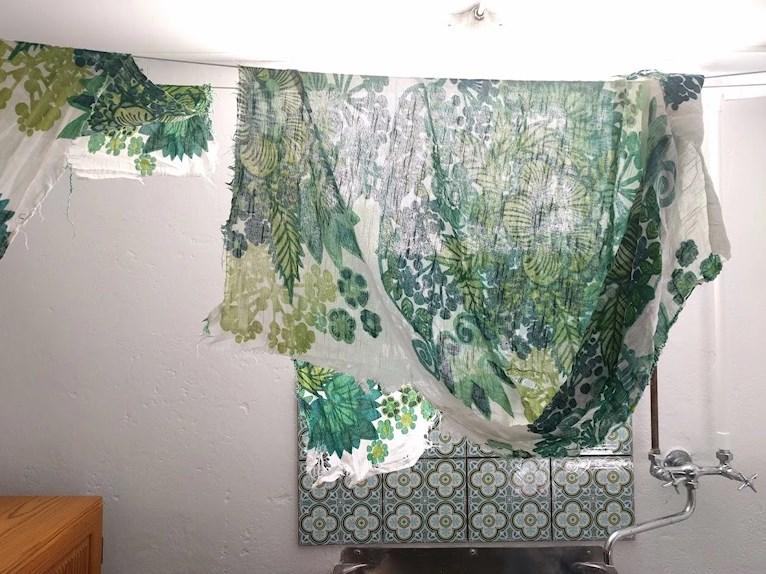 Återbruk av retro vintage tyg avsprättat från soffa pompeja pompeija grönt blommigt trasigt och slitet ska bli kuddar hänger på tork i tvättstuga nyrenoverad.