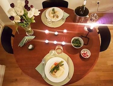 Runt matbord med blommor, middag och gott vin.