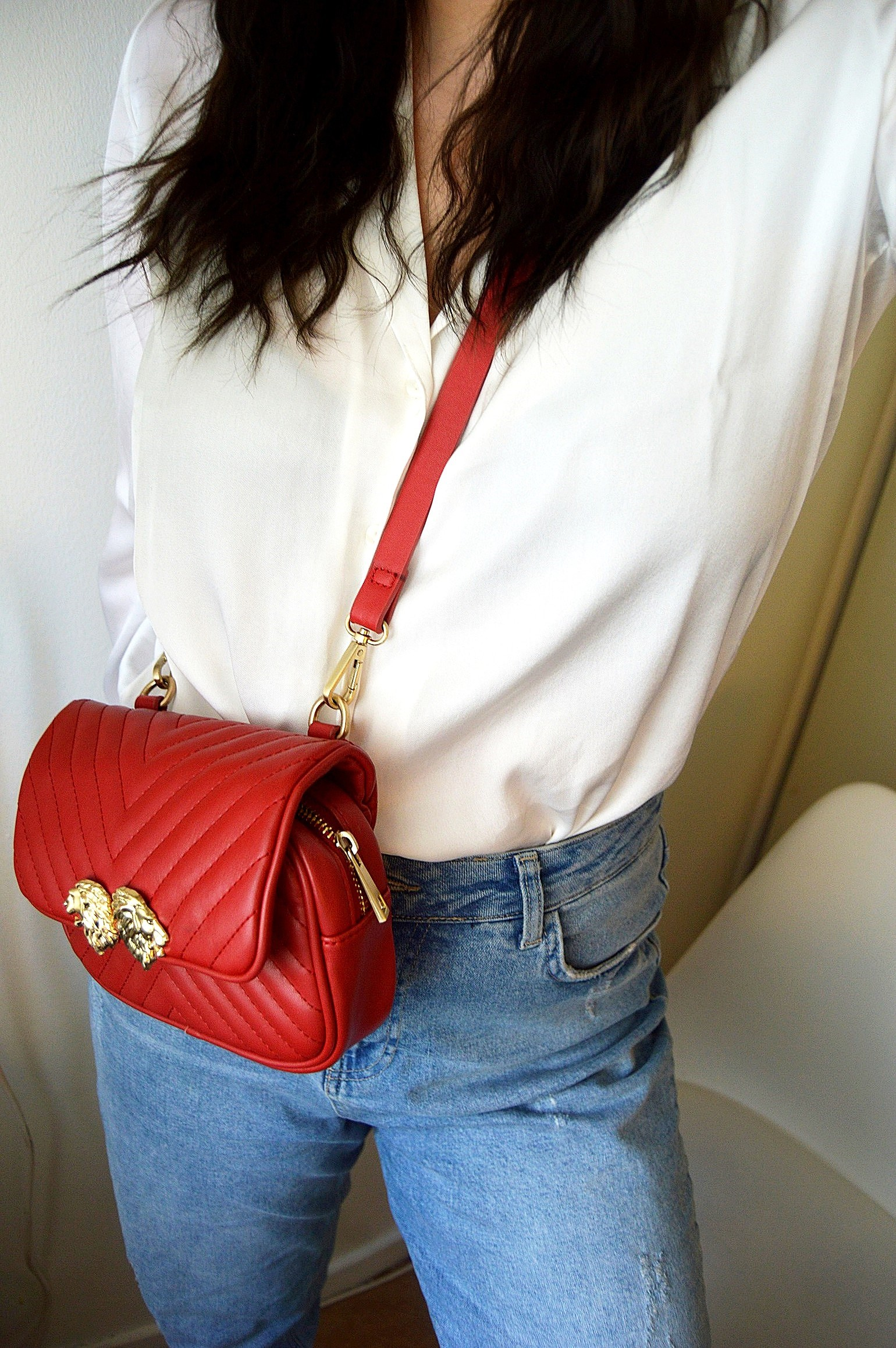 White shirt, red bag, blue jeans.