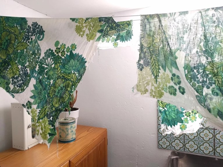 Återbruk av vintage retro tyg avsprättat från soffa pompeja pompeija grönt blommigt trasigt och slitet ska bli kuddar på tork på lina i tvättstuga.
