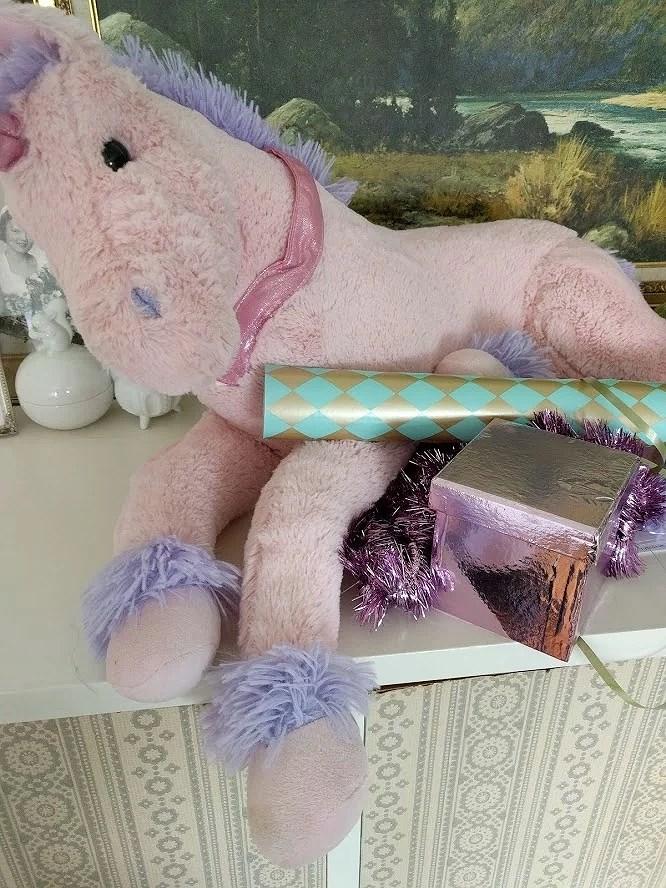 Rosa mjukisdjur häst enhörning med presentpapper och glitter.