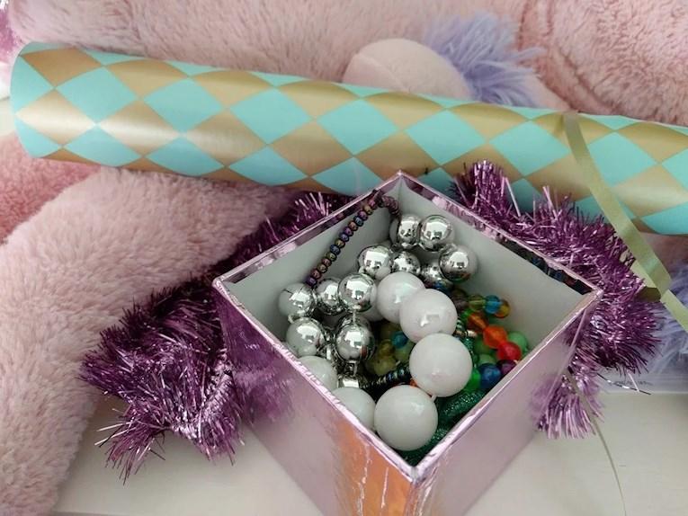 Lila julgransglitter och glansig låda med pärlhalsband.