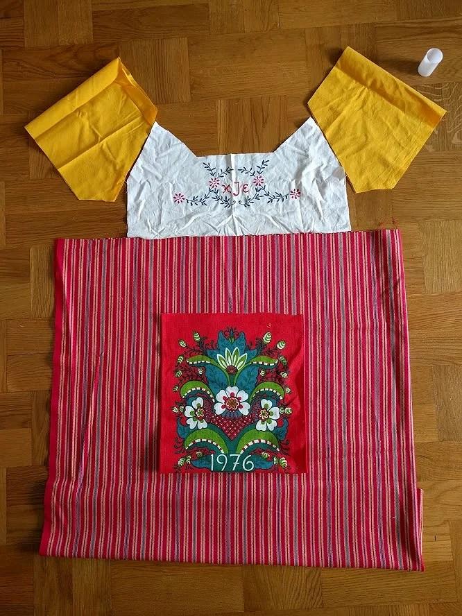 Tillklippta tygbitar tänkta att bli en klänning inspirerad av folkdräkt.