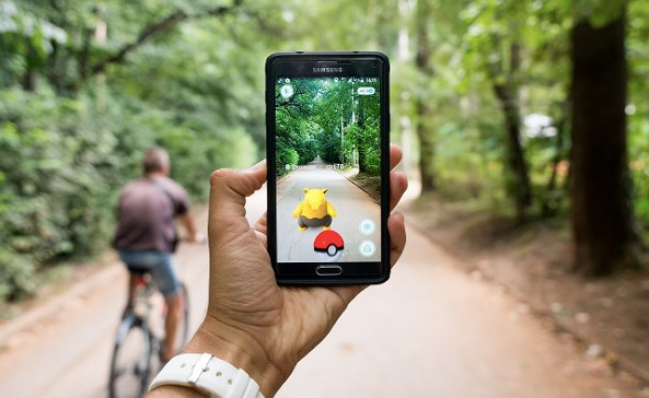 Playing Pokemon Go outside on a bike path surrounded by trees