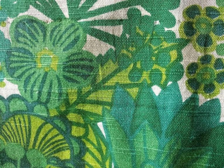 Närbild på grönt retro vintage tyg pompeja pompeija blommigt 70tal 60tal på vit botten.