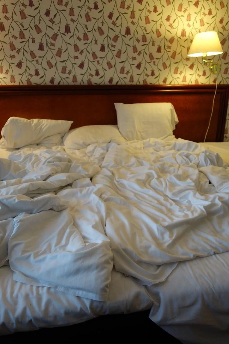 Billigaste hotellet i Stockholm Best western Capital obäddad säng i rum med blommiga tapeter.