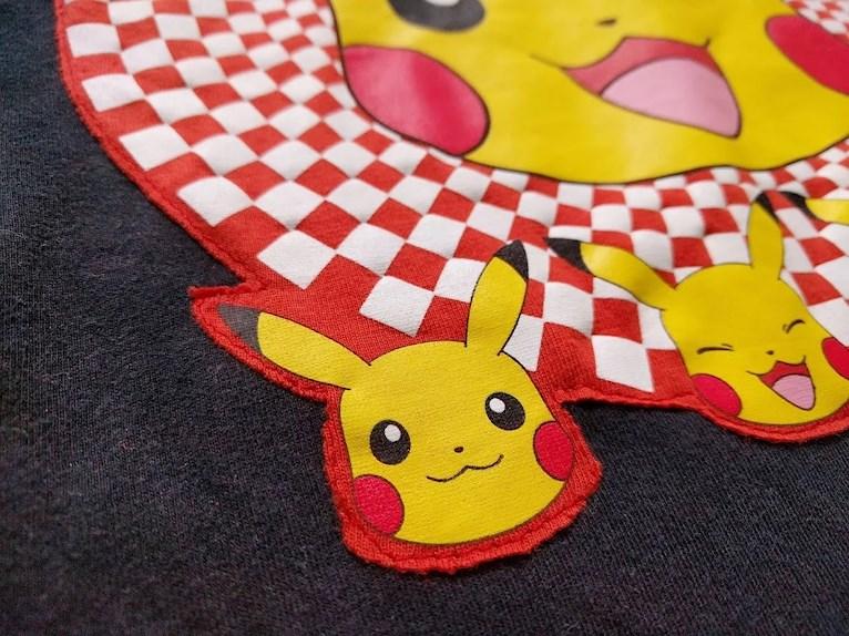 Ny barntröja med Pokémon från gammal tröja återbruk av tryck som sys fast med maskin på loppisfyndad enfärgad närbild inte perfekt söm.