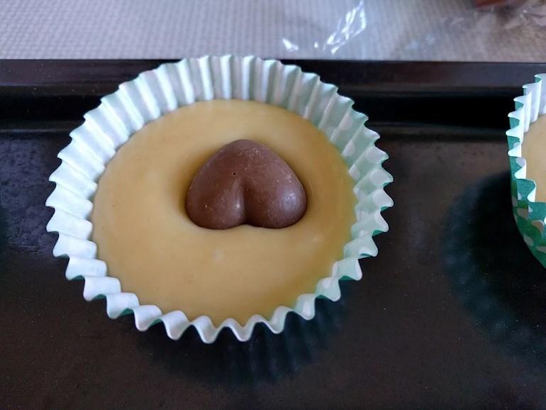 Närbild på muffinsform eller bullform med smet och chokladhjärta i.