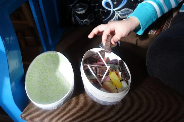 Barnhand som plockar godis ur påskägg.