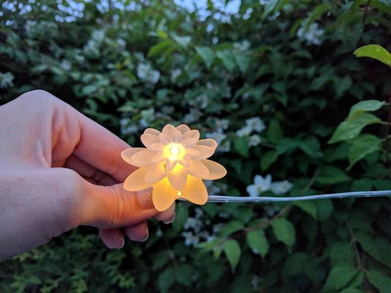 Ljusslinga i form av blommor ovanför renoverat grythyttan bord trädgårdsbord framför häck av schersmin.