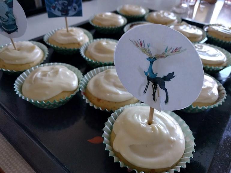 Muffins cupcakes med glasyr och dekoration av papper på plåt.