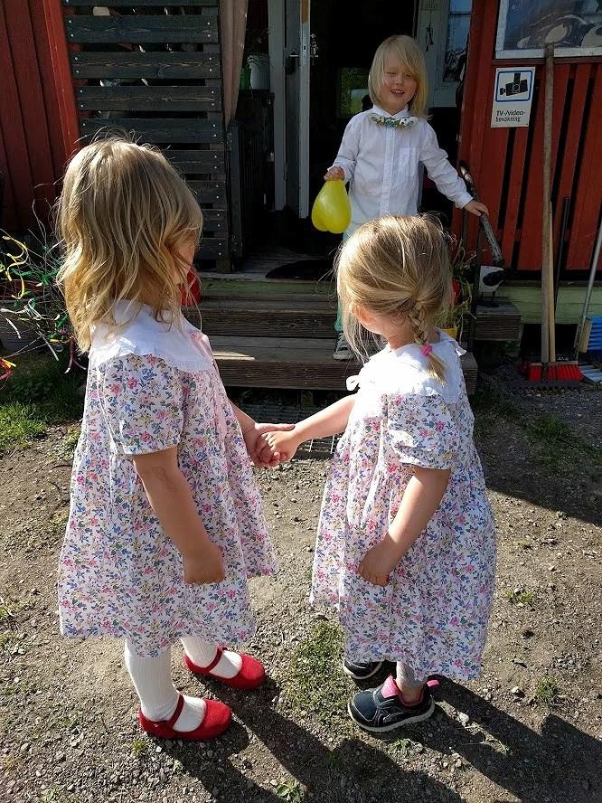 Små flickor i likadana blommiga sommarklänningar.