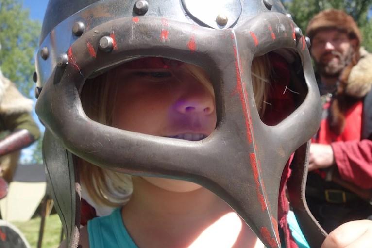 Ett barn provar en riddarhjälm med spetsig näbb.